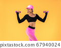Sporty woman in fashionable sportswear does the exercises with dumbbells. Photo of muscular woman on yellow background. 67940024