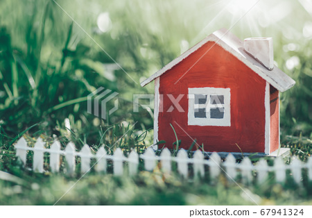 red wooden house model on the grass 67941324