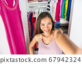 Selfie Asian girl taking photo with mobile phone of herself in closet dressing room at home trying on outfit. Clothes fashion style. Shopping girl using smartphone fashion app posting on social media 67942324
