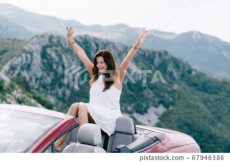 Happy woman sits in a red convertible car with a beautiful view 67946386