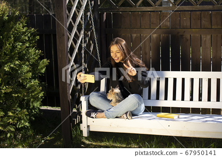 Happy beautiful smiling woman sitting on swing with pet, making video call 67950141