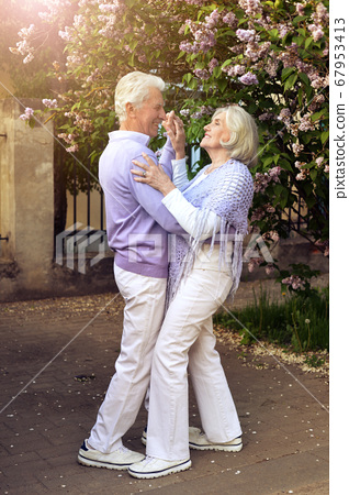 Beautiful senior couple dancing in the park by lilacs 67953413