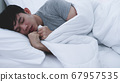 Asian man feeling cold while sleeping at home. 67957535