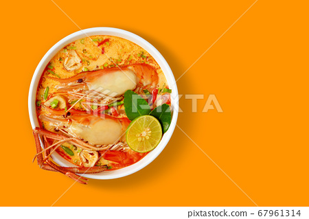Prawn and lemon grass soup with mushrooms or Tom Yum Kung is Thai food cuisine is most popular in Thailand isolated top view on orange table. 67961314