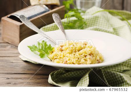 Italian traditional risotto with saffron and ham 67965532