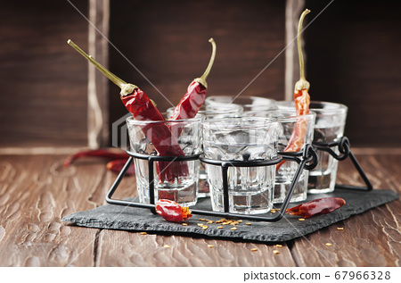 Shot of vodka and chili peppers 67966328