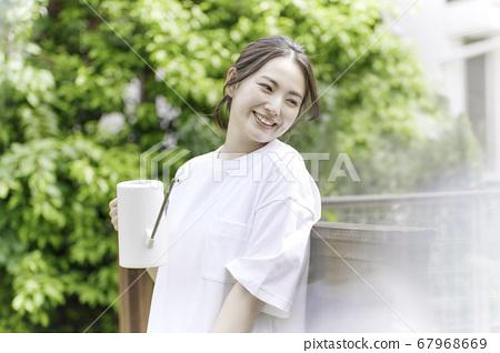 一個年輕的女人,用白色的噴壺在花園裡[夏天的圖像] 67968669