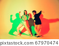Young man and woman dancing hip-hop, street style isolated on studio background in neon light 67970474
