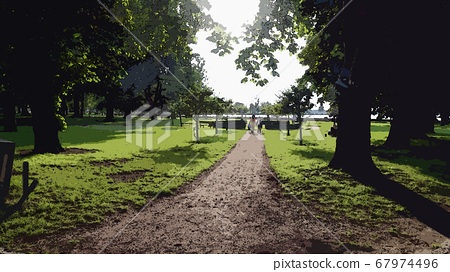 Digital painting style representing a young woman with a boy walking on the tree-lined avenue towards the sea 67974496