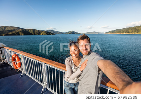 Cruise couple tourists taking selfie on New Zealand travel. People traveling on ferry boat Marlborough sounds taking self-portrait picture with mobile phone smiling at camera. 67982589