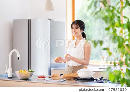 주방에서 요리를하는 젊은 여성 67983039