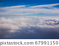 Aerial sky and fluffy clouds background. View from airplane porthole 67991150