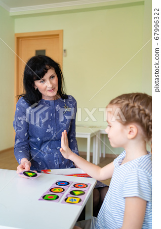 teacher with child play cards geometric shapes. 67996322