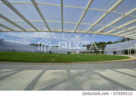 運動場的草坪和透光的玻璃建築物 67999212