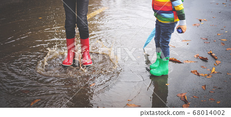 Child walking in wellies in puddle on rainy weather 68014002