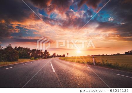 Asphalt road and dividing lines at sunset 68014183