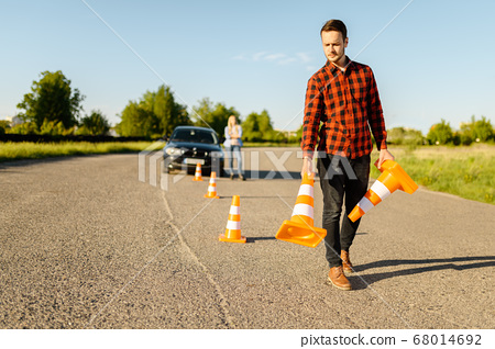 Male instructor puts cones on road, driving school 68014692