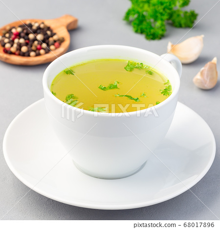Chicken broth in a white cup with chopped parsley 68017896