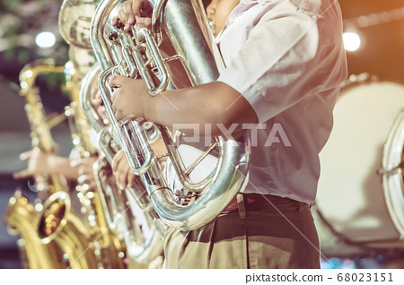 Male student with friends blow the euphonium with the band for performance on stage at night. 68023151