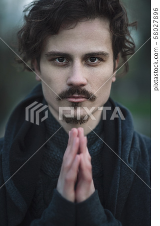 Handsome young curly man sincerely praying. 68027896