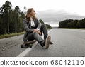 Handsome man in office suit with longboard walking down road in city outskirts. 68042110