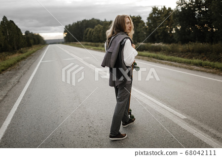 Handsome man in office suit with longboard walking down road in city outskirts. 68042111