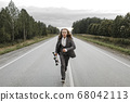 Handsome man in office suit with longboard walking down road in city outskirts. 68042113
