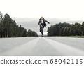 Man in office suit is riding skateboard longboard down road outside the city. 68042115