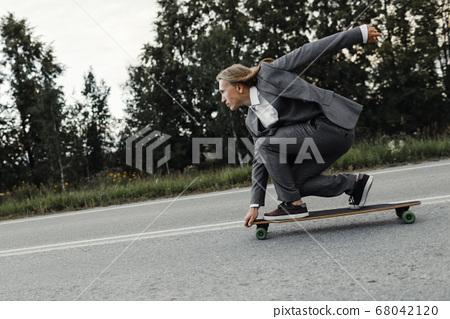 Man in office suit is riding skateboard longboard down road outside the city. 68042120