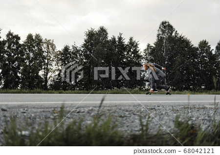 Man in office suit is riding skateboard longboard down road outside the city. 68042121