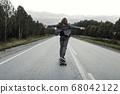 Man in office suit is riding skateboard longboard down road outside the city. 68042122