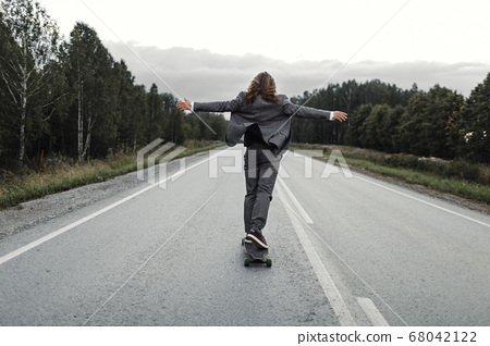 Man in office suit is riding skateboard longboard down road outside the city. 68042122