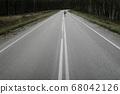 Man in office suit is riding skateboard longboard down road outside the city. 68042126