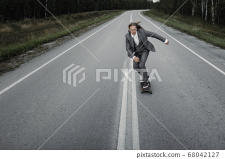 Man in office suit is riding skateboard longboard down road outside the city. 68042127