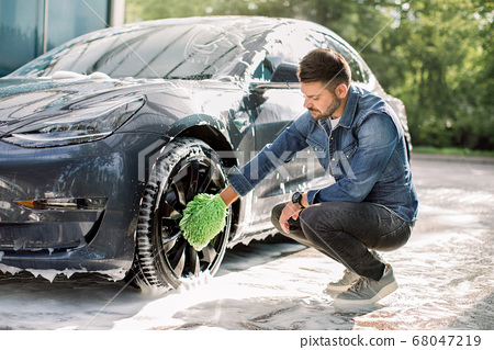 Luxury modern electric car in soap foam outdoors at car wash service. Side view of handsome young Caucasian man using green microfiber car wash mitt for cleaning rims outdoors. 68047219