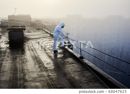 Worker scientist wearing protective coverall and gas mask doing ecological tests on the roof 68047625