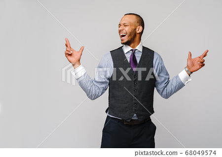young funny african-american businessman crossing fingers, wishing, hoping for best, miracle over grey background 68049574