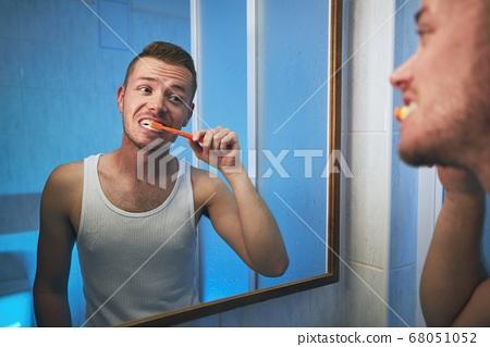 Man brushing teeth in home bathroom 68051052