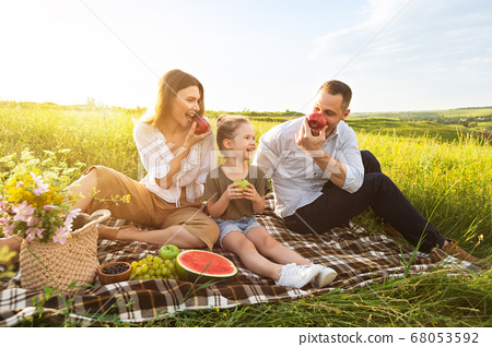 Young family playing with fruits on a picnic outdoor 68053592