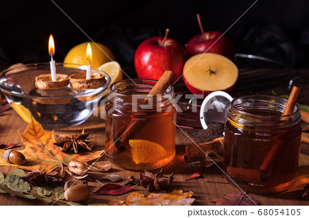 Dark wooden table with 2 glasses of tea with fall, autumn decoration  68054105
