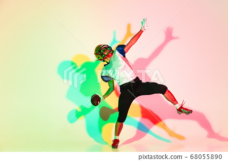 American football player isolated on gradient studio background in neon light with shadows 68055890