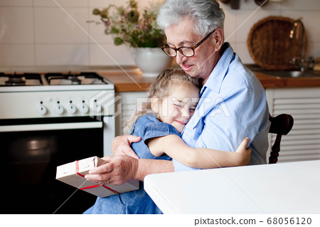Child is giving gift box to grandmother. Kid and senior woman are hugging in cozy home 68056120