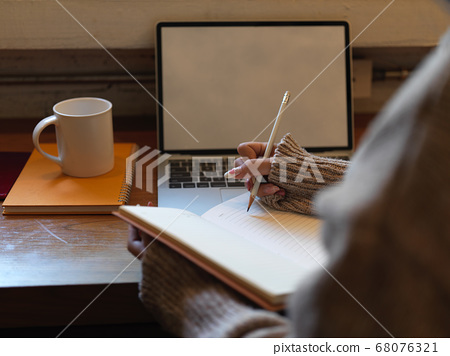 Female writing no blank notebook while siting at 68076321