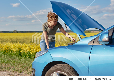 Woman repairs broken car with open hood on the 68079413