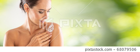 Beautiful young woman applying cream to her 68079506