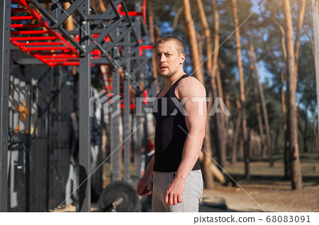 Athletic man standing outdoor gym workout. 68083091