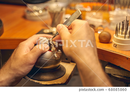 Male hands using a tool for stone setting 68085860