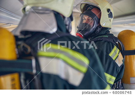 Two firemen with full equipments standing in the emergency place 68086748