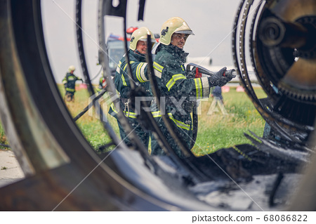 Firefighter in green fireproof uniform at the emergency operation 68086822