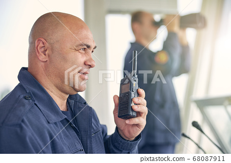 Smiling handsome worker holding walkie talkie in hand 68087911